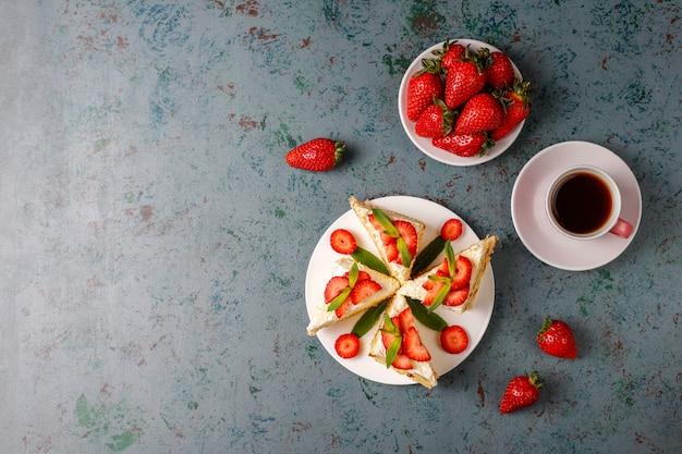 Fette casalinghe deliziose del dolce della fragola con le fragole crema e fresche, vista superiore