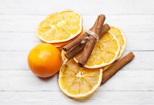 Fette d'arancia con cannella e mandarino su fondo di legno, vista dall'alto