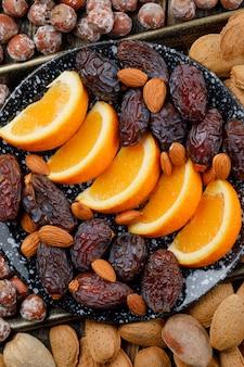 Fette d'arancia con datteri, mandorle e noci in un piatto sul vassoio di rame