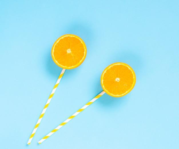 Fette d'arancia con tubuli, caramelle salutari su un bastone, lecca-lecca, sfondo azzurro, disposizione piatta, minimalismo