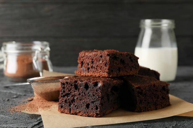 Fette del dolce di cioccolato, bottiglia di latte e filtro con polvere sul nero, fine su