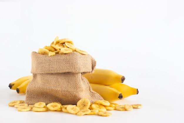 Fette della banana secca e della banana nella borsa del sacco con lo spazio della copia isolato su bianco