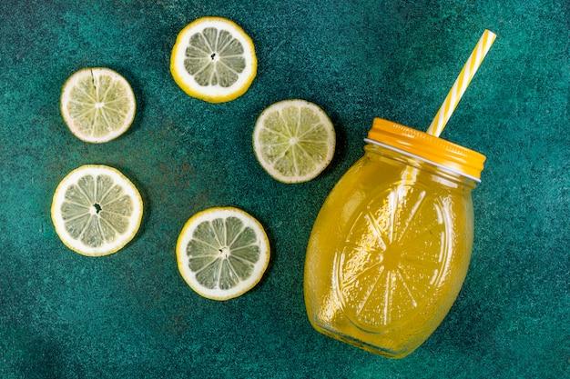 Fette della calce di vista superiore con le fette del limone e il succo di arancia su verde