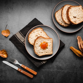 Fette della raccolta di vista superiore di pane affettato con le foglie di autunno
