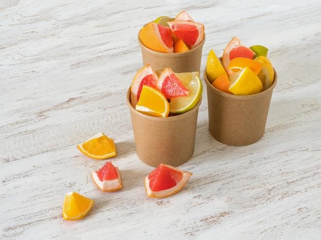 Fette di agrumi in un bicchiere di carta ambientale. bevanda di vitamina c. rafforzare il concetto di sistema immunitario