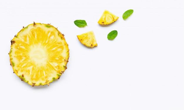 Fette di ananas con foglie di menta su sfondo bianco.