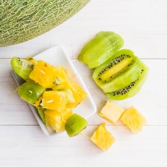 Fette di ananas e kiwi sul piatto sopra la superficie in legno