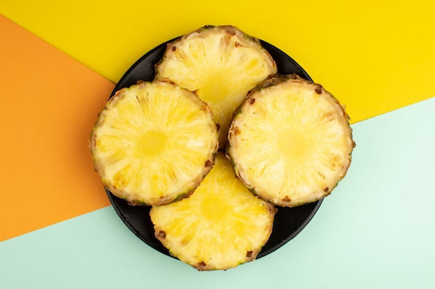 Fette di ananas fresche maturi succosi anelli succosi all'interno della banda nera su un pavimento colorato