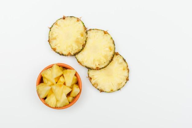 Fette di ananas in una ciotola di argilla su un bianco. vista dall'alto.