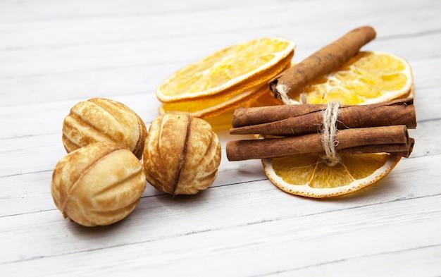 Fette di arancia con cannella e biscotti su uno sfondo in legno chiaro