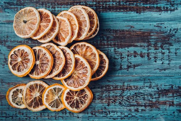 Fette di arancia essiccate su un tavolo di legno, fuoco selettivo e immagine tonica. tavolo in legno blu rustico