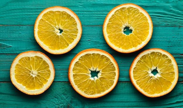 Fette di arancia secche su un fondo di legno turchese. vista dall'alto.
