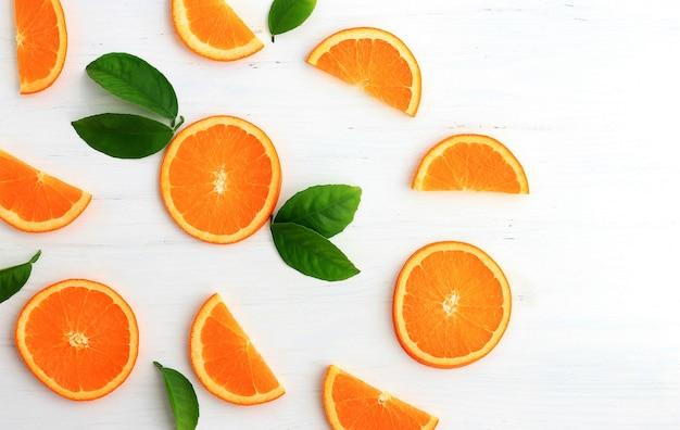 Fette di arancia su sfondo bianco. vista piana, vista dall'alto.