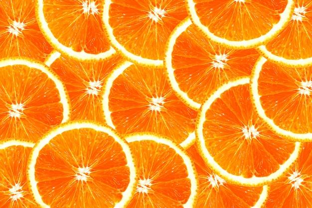 Fette di arancia succose fresche si sovrappongono per lo sfondo