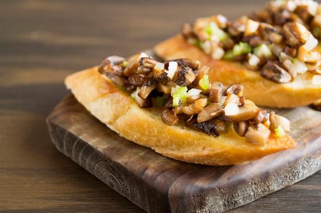 Fette di baguette fritte con funghi, aglio ed erbe aromatiche.