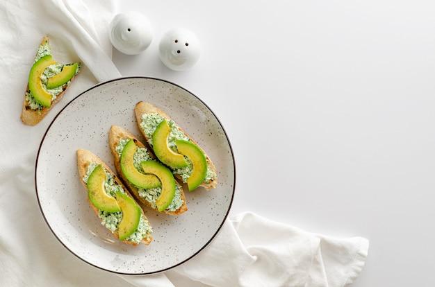 Fette di baguette tostate con ricotta, spinaci e avocado sul tavolo bianco