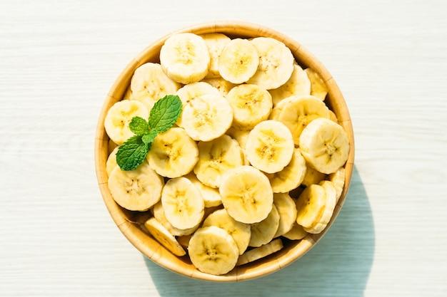 Fette di banana gialla cruda in ciotola di legno