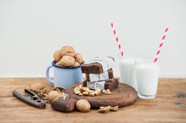 Fette di brownie al cioccolato avvolte in carta e stanche con la corda, bicchieri da latte, cannucce a strisce, tazza di smalto di noci sul tavolo di legno rustico, bianco