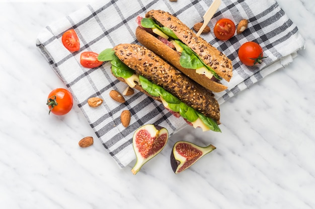 Fette di fichi; pomodori ciliegini; mandorle con hot dog freschi sopra un panno da cucina su sfondo bianco con texture