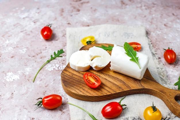 Fette di formaggio di capra su tavola di legno con rucola, pomodorini. pronto a mangiare.