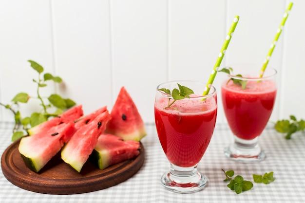 Fette di frutta a bordo e bicchieri con cocktail sul tovagliolo