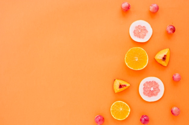 Fette di frutta d'arancia; pompelmo e pesca con uva su uno sfondo arancione