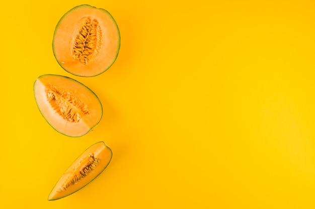 Fette di frutta del cantalupo contro il contesto giallo