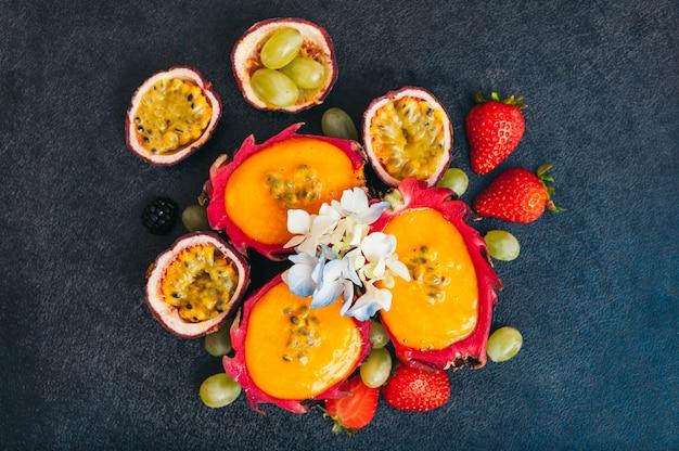 Fette di frutta del drago, fragola matura rossa e uva su sfondo scuro.