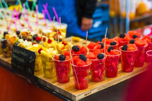 Fette di frutta fresca nella tazza di plastica usa e getta in vendita
