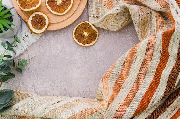 Fette di limone essiccate con strisce tessile su sfondo concreto