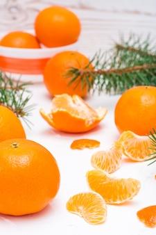 Fette di mandarino purificate, mandarini interi e rami di abete su un tavolo bianco