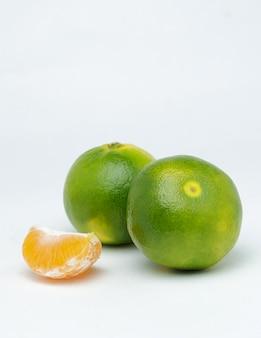 Fette di mandarino su una superficie bianca