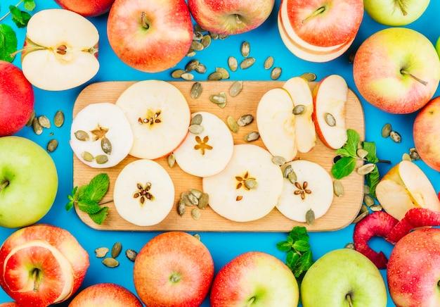 Fette di mela; semi di zucca e foglie di menta su sfondo blu