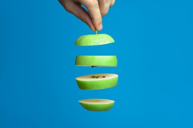 Fette di mela verde su un blu. uno dei pezzi nella mano maschile