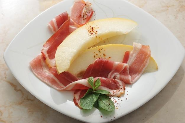 Fette di melone avvolte in pancetta con foglie di menta su marmo