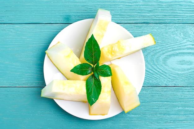 Fette di melone su un piatto e un rametto di basilico su un tavolo di legno in legno piatto disteso