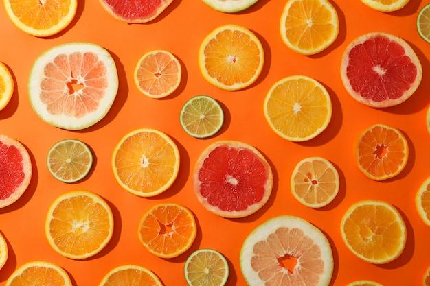 Fette di molti agrumi su fondo arancio, vista superiore