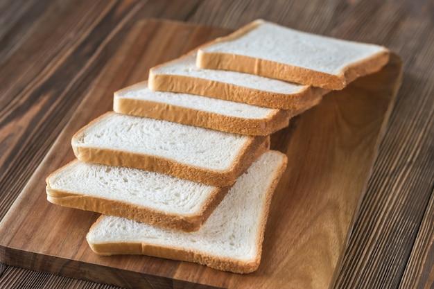 Fette di pane bianco su una tavola di legno