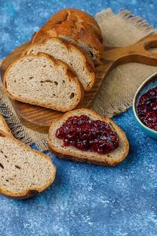 Fette di pane con marmellata di lamponi, spuntino sano facile, vista dall'alto