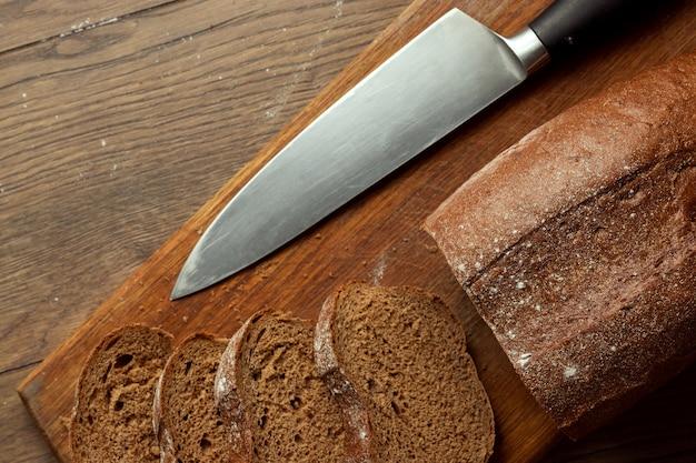 Fette di pane di segale e un coltello primo piano, su un tagliere di legno