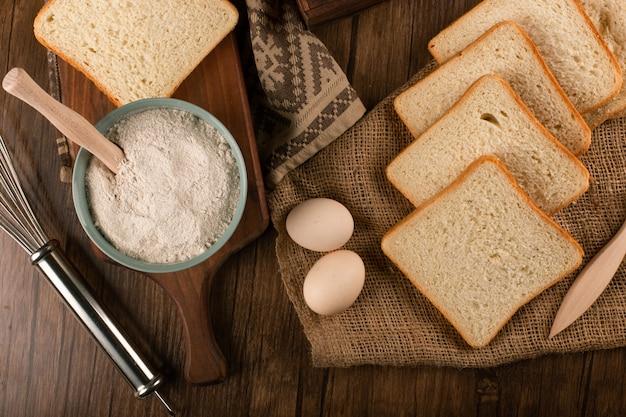 Fette di pane e ciotola di farina con le uova