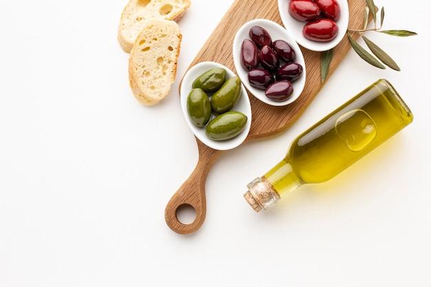 Fette di pane e olive verdi rosse viola con la bottiglia di olio d'oliva