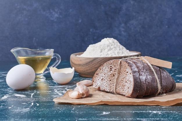 Fette di pane nero con olio sulla tavola blu.