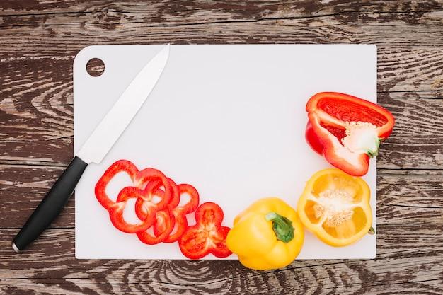 Fette di peperoni rossi con un coltello affilato sul bordo bianco sopra il ripiano del tavolo in legno