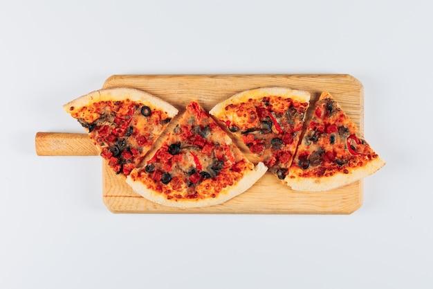 Fette di pizza in un tagliere per pizza su uno sfondo di stucco bianco brillante. disteso.