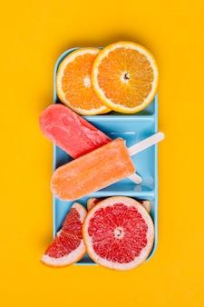 Fette di pompelmo e arancia con gelato piatto distesi