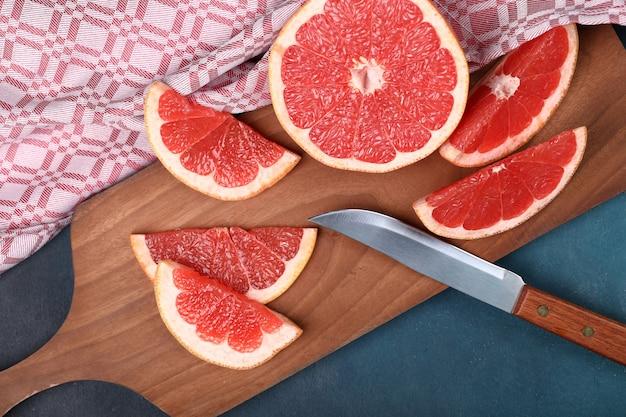 Fette di pompelmo fresche rosse su una tavola di legno con un coltello.