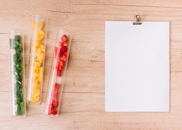 Fette di rosso; peperone verde e giallo in contenitori aperti della provetta vicino al libro bianco sulla tavola di legno