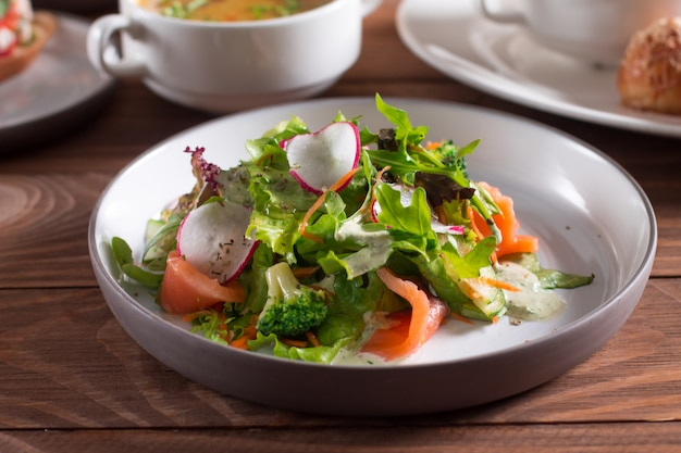 Fette di salmone con insalata di verdure fresche su un piatto.