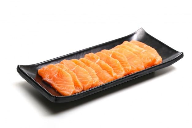 Fette di salmone nella piastra nera su sfondo bianco
